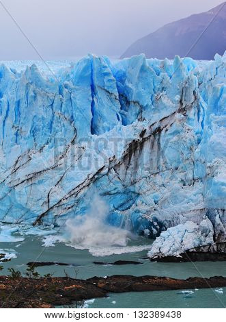 White-blue ice massif multimeter height rises over the lake. Giant lake Perito Moreno glacier