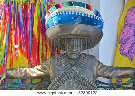 PUERTO VALLARTA MEXICO MAY 07 2016:  Sculputre depicts a Mexican Revolutionary soldier maybe it is supposed to depict Emiliano Zapata sitting on a bench with arms stretched out casually