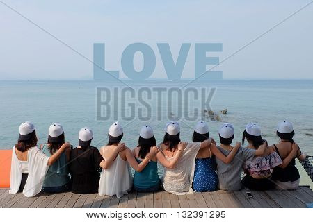 women friend group sit make arm hug hold around their friend's shoulder on wooden pier. They wear same design white and black color caps. looking at LOVE word on blue sea sky.