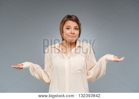 Confused young pretty girl standing and shrugs shoulders with her arms out isolated gray background