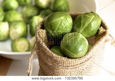 Brussel sprouts in a brown hessian bag.