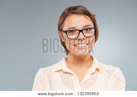 Close-up portrait of a smiling beautiful girl isolated on the gray background