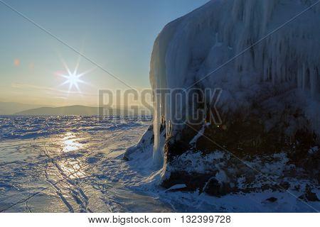 Dawn and icy island Lohmaty. Beautiful winter landscape in the Lake Baikal.