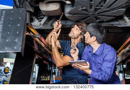 Mechanics Discussing Over Digital Tablet Under Lifted Car