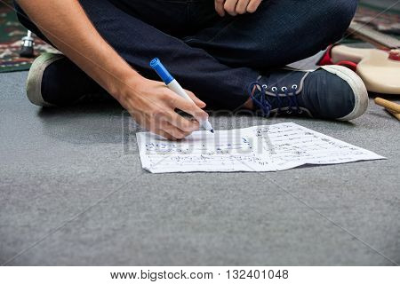 Low Section Of Drummer Writing Notes While Sitting On Floor