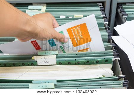 Hand holding report file in filing cabinet