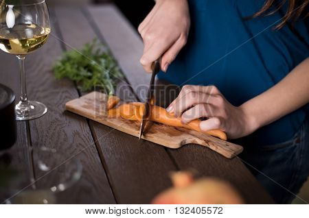 Close up of a young woman cutting carrots in kitchen. Woman preparing salad wit various vegetables. Young woman cooking food. Closeup of female hands cutting carrot on chopping board.