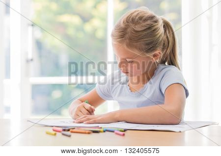 Happy little girl drawing with pencils at home. Portrait of concentrate girl coloring with crayons on copybook. Little girl painting on table.