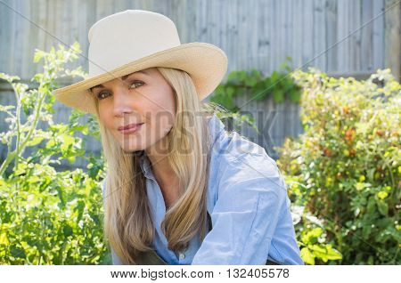 Satisfied woman gardening in her vegetable garden. Senior woman in garden wearing straw hat and thinking. Portrait of a woman in garden thinking and looking away.
