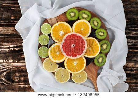 Slices Of Citrus Fruits On Chopping Board With Silk