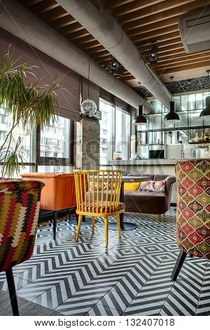 Nice hall in a loft style in a mexican restaurant with open kitchen on the background. In front of the kitchen there are wooden tables with multi-colored chairs and a brown sofa. On the sofa there are color pillows. In the kitchen there is a rack