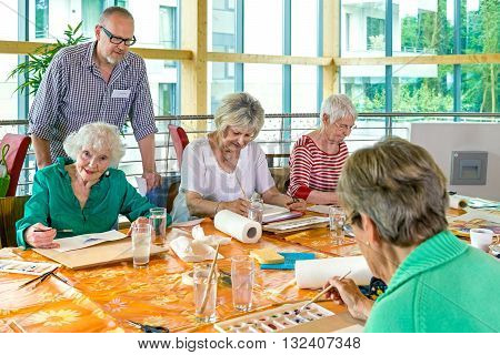 Male bearded instructor wearing eyeglasses overseeing four cute senior students painting in class