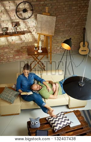Young couple resting on sofa at home, woman reading a book, man lying and sleeping on lap. Photographed from above.