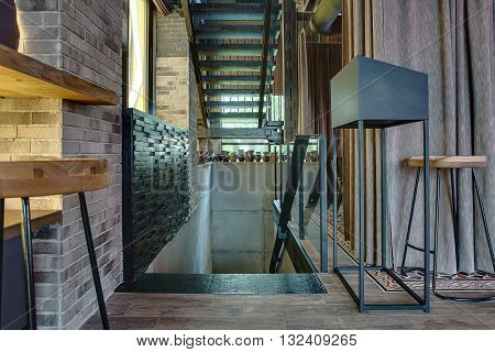 Dark stairs in a hall in a restaurant in a loft style. On the left there is a wooden rack with a wooden chair, a brick wall with a window with print and curtain. On the right there is a black metal stand, a wooden chair, curtains.