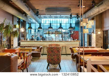 Glowing interior in a loft style in a mexican restaurant with open kitchen on the background. In front of the kitchen there are wooden tables with multi-colored chairs and sofas. On the sofas there are color pillows. In the kitchen there is a rack