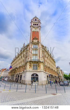 Lille, France - June 3, 2015: Famous town hall clock tower as seen from street underneath, beautiful architecture and nice blue sky background.