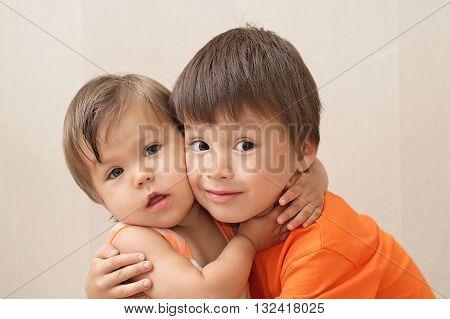 Older Brother And Younger Sister Hugging Portrait