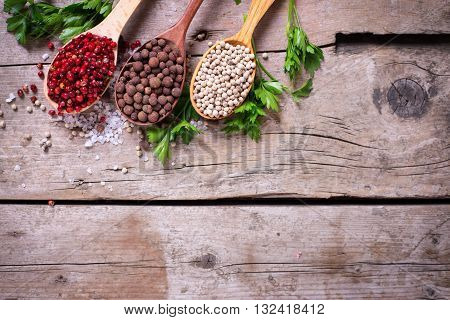 Seasoning for cooking. Red white and allspice pepper in wooden spoons on aged wooden background. Selective focus. Flat lay. Top view. Place for text.