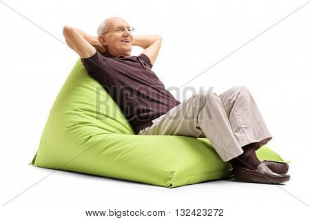 Relaxed senior gentleman sitting on a comfortable green beanbag isolated on white background