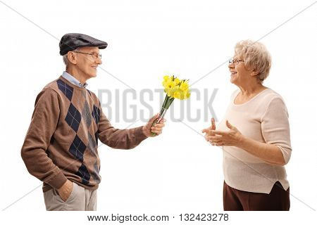 Thoughtful senior man giving flowers to a joyful senior lady isolated on white background