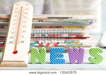 Hot news creative symbol with thermometer and newspaper