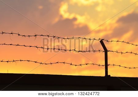 Barbed wire fence with sky sunset time