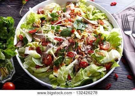 Asian beef salad with cucumber, lettuce and chilli in big white plate on wood background