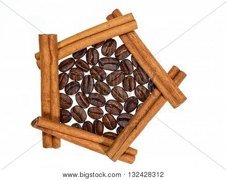 Roasted coffee beans in pentagon of cinnamon sticks on white background