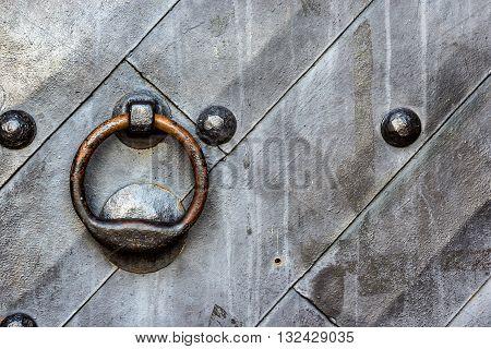 Old black metal door in temple gate with ring knocker