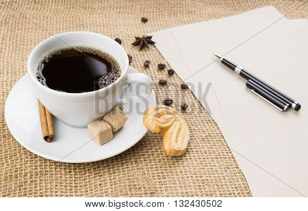 Cup of black coffee with foam cookie brown sugar craft paper pen coffee beans anise star and cinnamon stick on sackcloth background