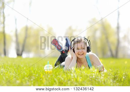 Young woman lying on grass in Park listening to music on headphones
