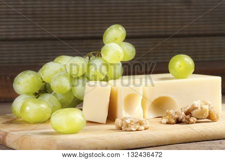Cheese with brush of grapes and walnuts on a wooden table.  Vintage style
