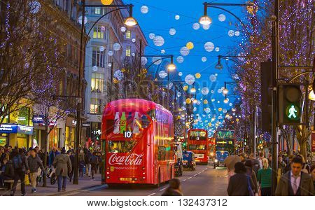 LONDON, UK - DECEMBER 30, 2015: Christmas lights decoration at Oxford street and lots of people walking during the Christmas sale, public transport, buses and taxies