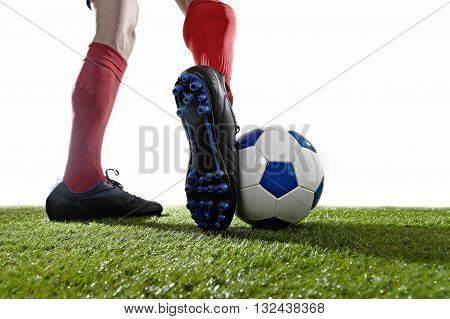 back view legs and feet of football player in red socks and black shoes running and dribbling with the ball playing on green grass pitch isolated on white background