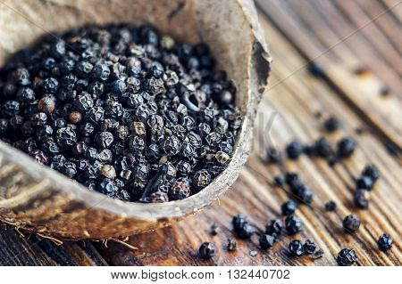 Whole black Peppercorns on old wooden table. Close up, selective focus.