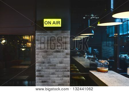 Half-lighted room in a mexican restaurant. There is a brick wall with glowing signboard and windows. On the right there is a light rack with jar on it and glowing lamps over it. Other side of the room reflected in the windows. Horizontal.