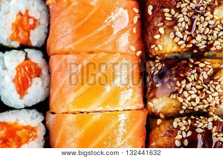 Sushi Set sashimi and sushi rolls served on dark plate. Image of Japanese food on dark background. Top view.