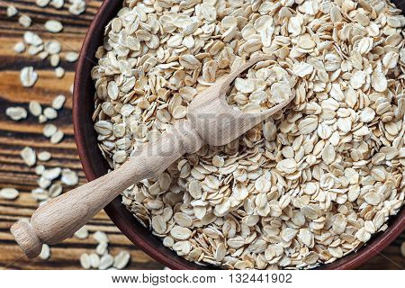 Food. Oatmeal on the table. Dry rolled oat flakes oatmeal in brown bowl on old wooden table.