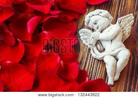 Closeup view of beautiful cupid with the trumpet, angel decorative figurine near red rose petals on wooden background. Greeting card . St Valentine's Day concept. Horizontal picture with copy space