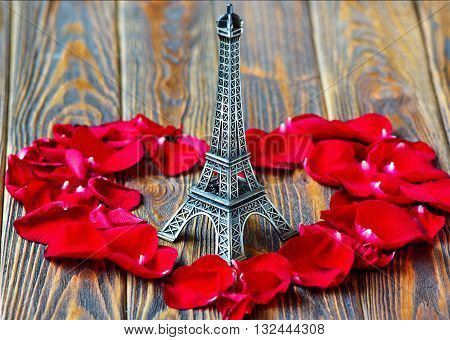 Eiffel tower statue and red rose petals on wooden background. Travel, love concept.