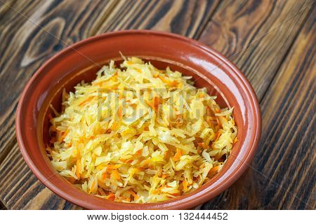 Fermented cabbage - Sauerkraut with herbs and spices on the wooden background. Cabbage stew in ceramic bowl.
