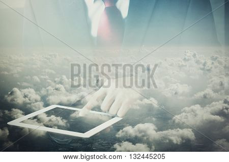 Double exposure of Businessman touching on tablet dissolved with clouds on the sky background.