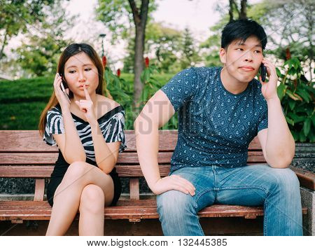 Girlfriend having secret and hiding from her boyfriend while using mobile phone