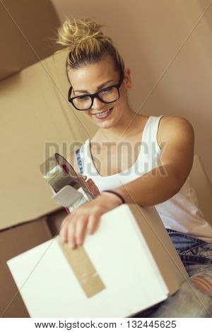 Young girl moving in a new appartment sitting on the floor surrounded with cardboard boxes packing and taping boxes