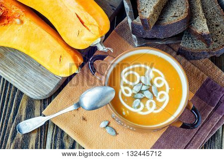 Roasted pumpkin soup with cream, fresh pumpkins and pumpkin seeds in plate on wooden background. Copy space