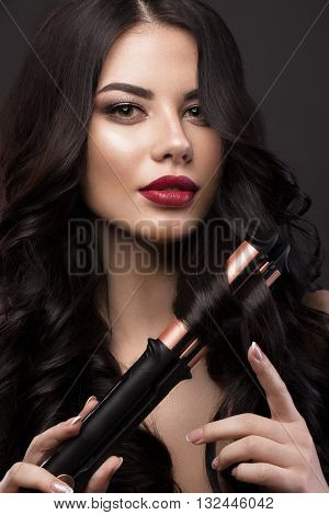 Beautiful brunette girl with a perfectly curls hair, curling and classic make-up. Beauty face. Picture taken in the studio.