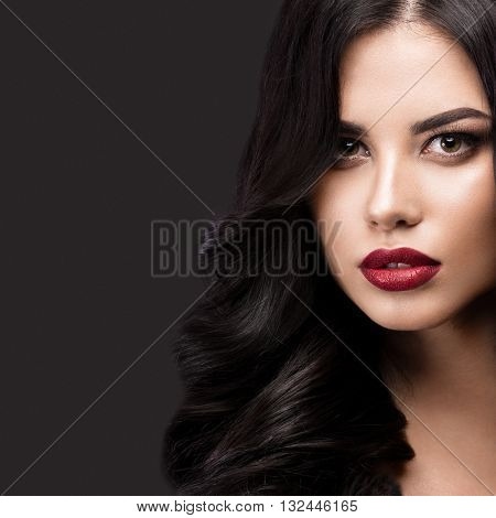 Beautiful brunette model with curls, classic makeup and red lips. The beauty of the face. Portrait shot in the studio on a gray background.