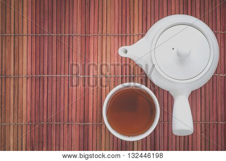 Cup of hot chinese tea and tea pot on bamboo mat plate
