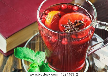 Hot red mulled wine in transparent cup on wooden background decorated with christmas spices, orange slice, fresh mint, cloves, anise and cinnamon sticks, close up.