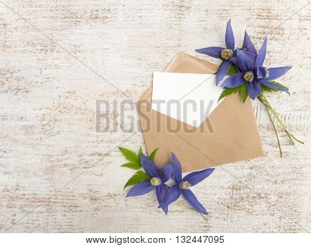 Kraft paper envelope with white blank card and blue clematis alpina flowers